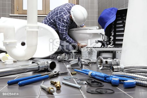 istock plumber at work in a bathroom, plumbing repair service, assemble and install concept 944254414