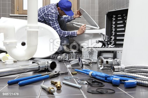 istock plumber at work in a bathroom, plumbing repair service, assemble and install concept 948721476