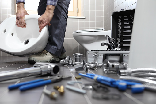 istock plumber at work in a bathroom, plumbing repair service, assemble and install concept 948721478
