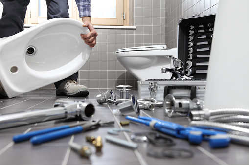istock plumber at work in a bathroom, plumbing repair service, assemble and install concept 948721484