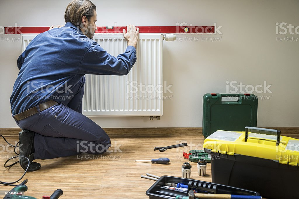 Plumber at work, installing new heater, measuring level royalty-free stock photo