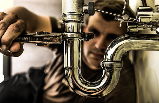 Plumber at work Plumber using a wrench to tighten a siphon under a sink. pipefitter stock pictures, royalty-free photos & images
