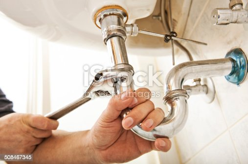 Plumber using a wrench to tighten a siphon under a sink