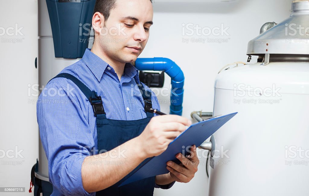Plumber at work Technician servicing an hot-water heater Adult Stock Photo