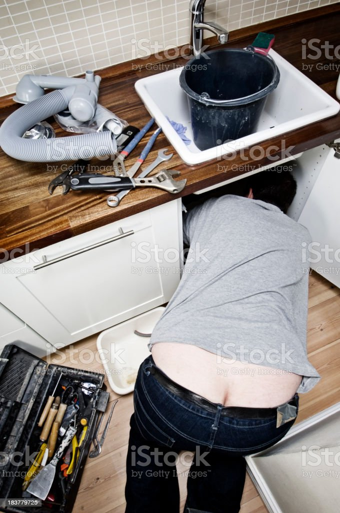 Plumber At Work Under a Sink Unit royalty-free stock photo