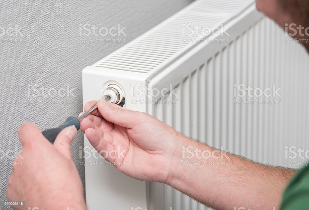 Plumber bleeding a radiator valve stock photo