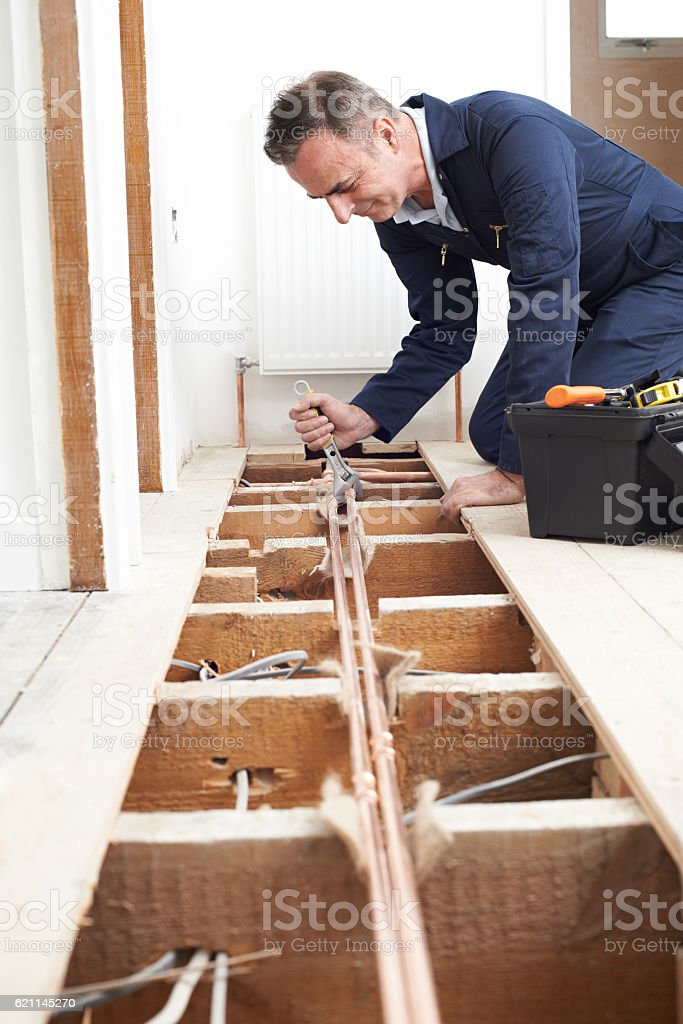 Plumber Fitting Central Heating System In House stock photo