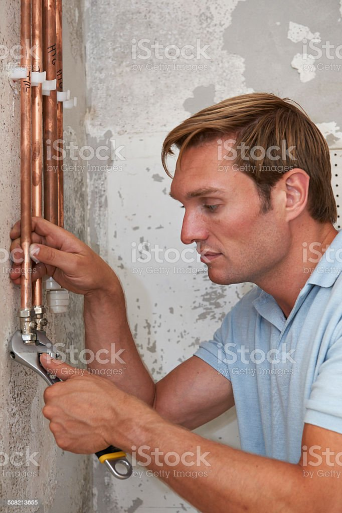 Plumber Fitting Pipes On Construction Site stock photo