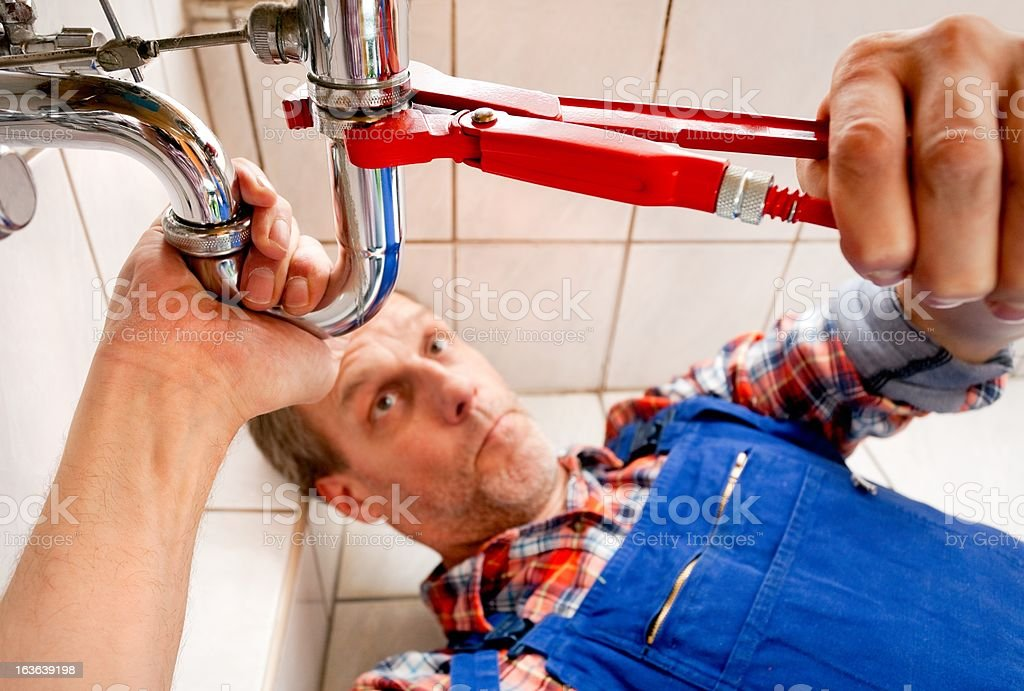 Plumber fixing a sink in bathroom stock photo