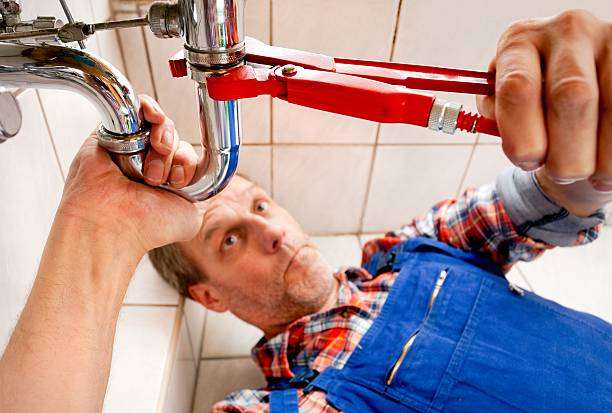 Plumber fixing a sink in bathroom Plumber at workPlumber at work pipefitter stock pictures, royalty-free photos & images