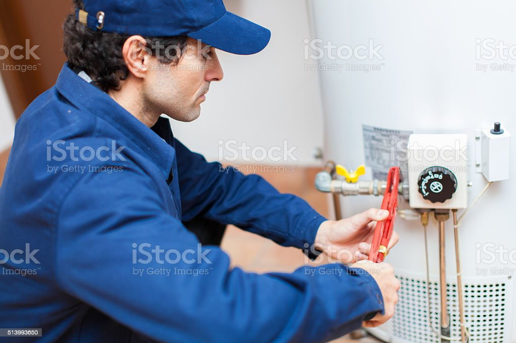 Plumber fixing an hot-water heater stock photo