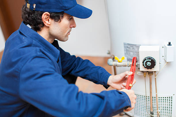 Plumber fixing an hot-water heater stock photo