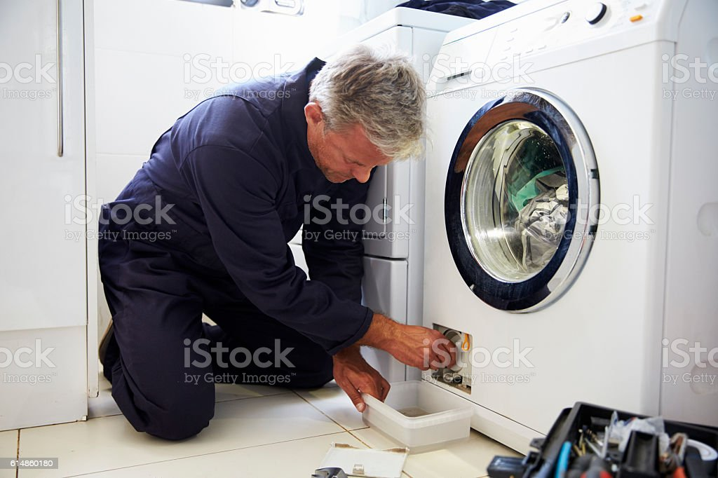 Plumber Fixing Domestic Washing Machine stock photo