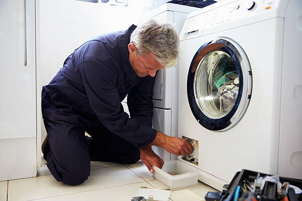 plumber fixing domestic washing machine - flicken stock-fotos und bilder