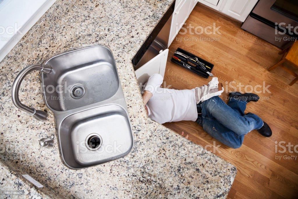 Plumber fixing kitchen sink stock photo