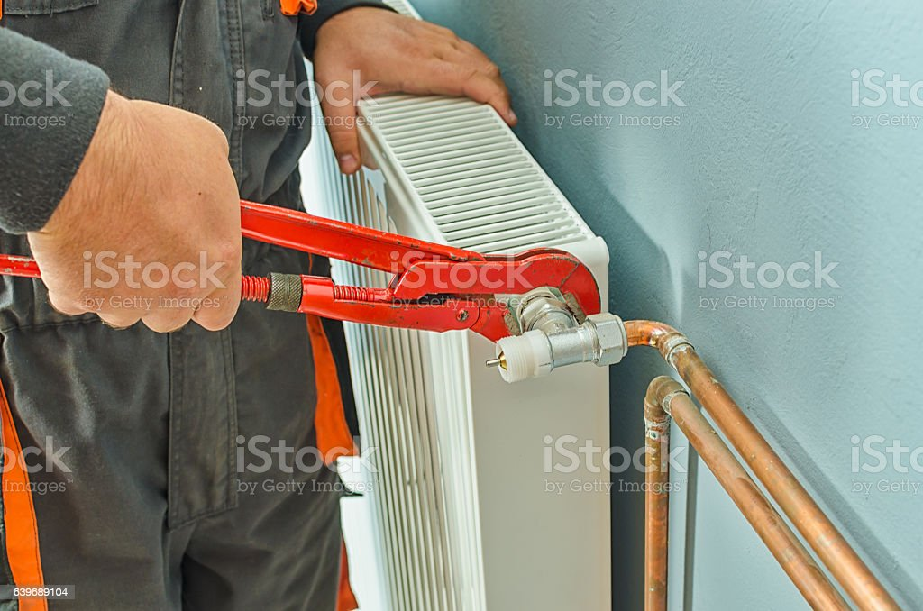 Plumber fixing radiator stock photo
