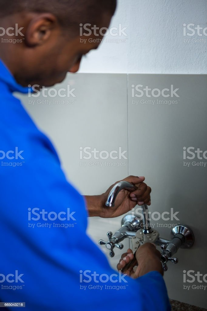 Plumber fixing the sink with wrench stock photo