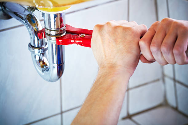 Plumber hands holding wrench and fixing a sink in bathroom stock photo