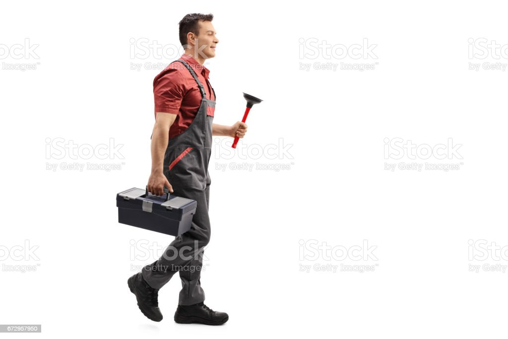 Plumber holding a plunger and a toolbox walking stock photo