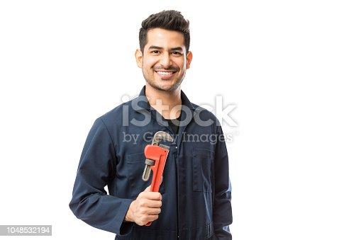 Handsome plumber holding Stillsons while smiling against white background