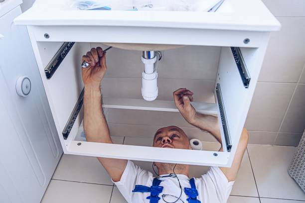 Plumber in work clothes is repairing or installing a bathroom sink stock photo