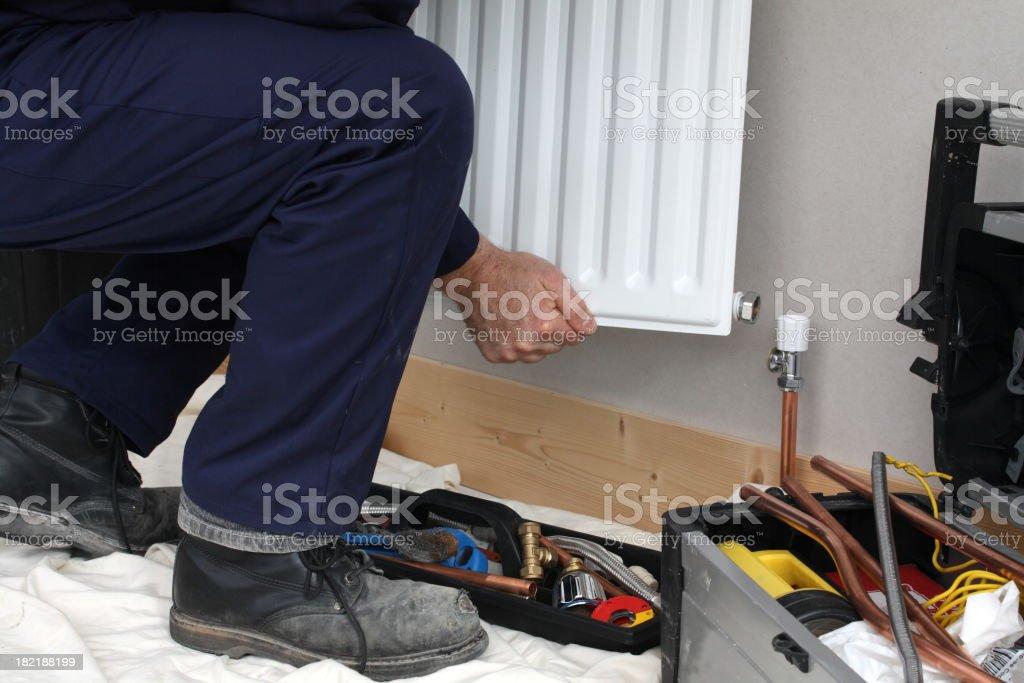 Plumber installing a new radiator. royalty-free stock photo