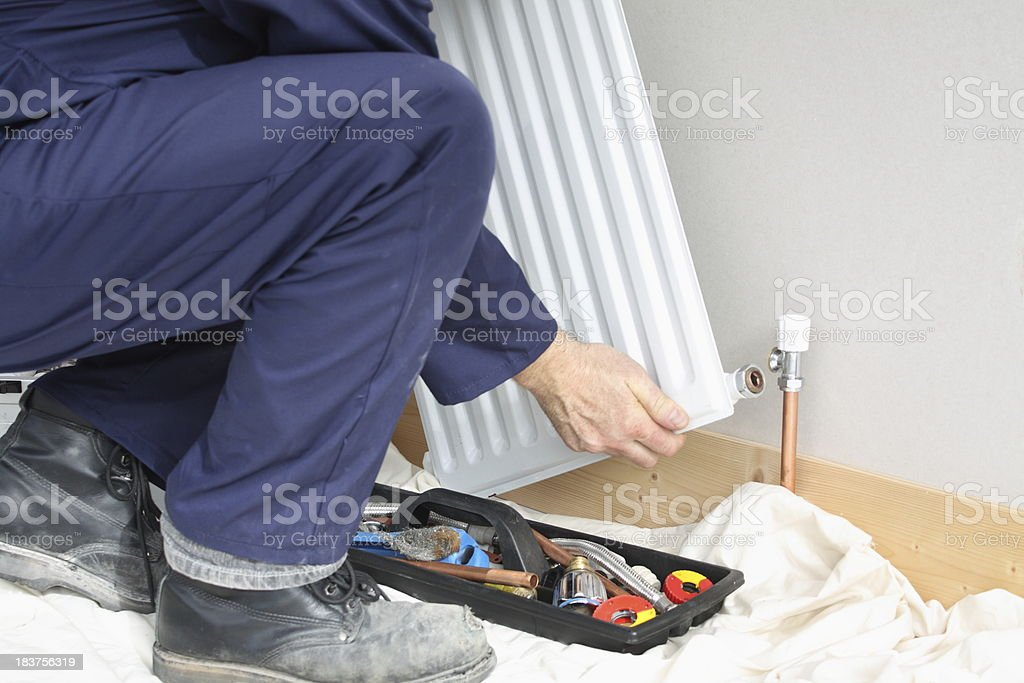 Plumber installing a radiator. stock photo