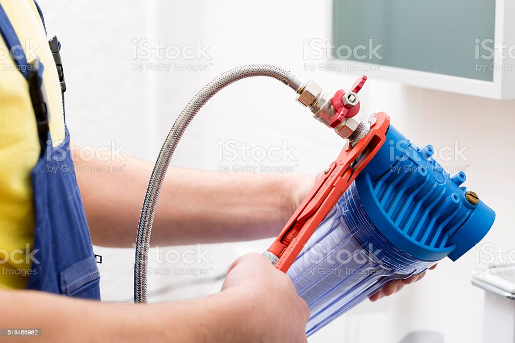 plumber installing new water filter stock photo