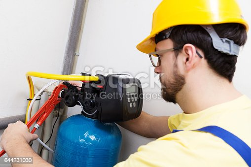 istock plumber installing new water filtration system 644231030