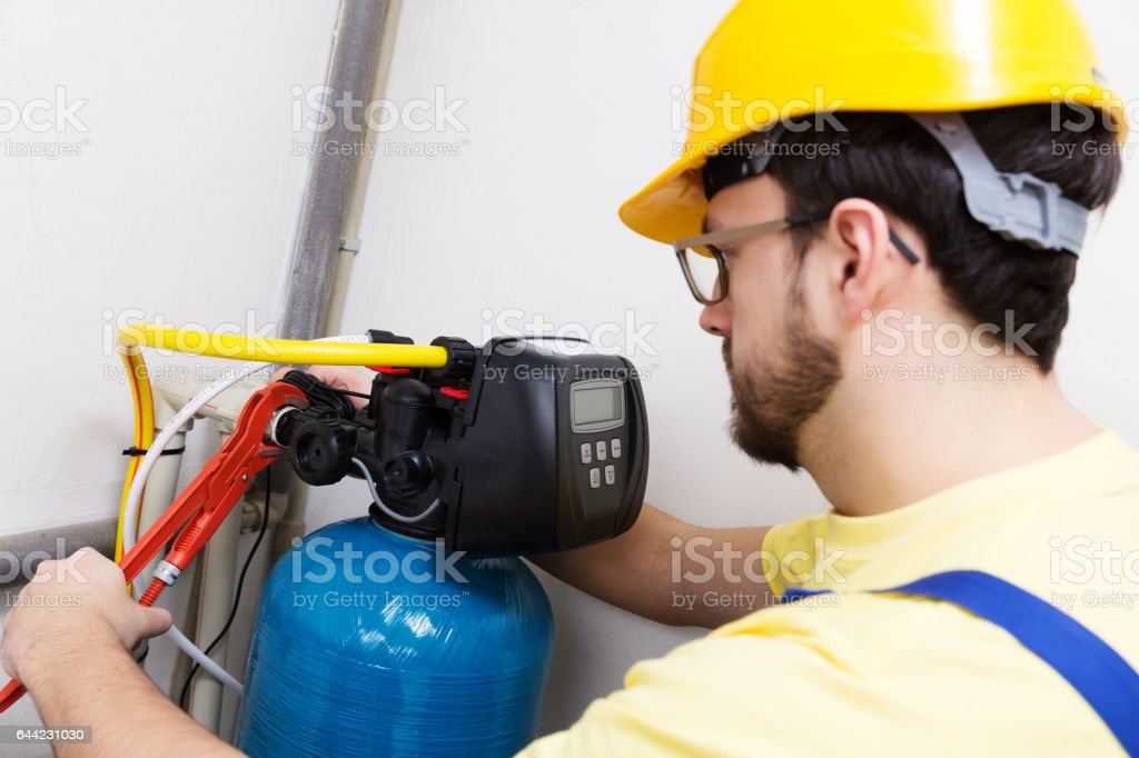 plumber installing new water filtration system stock photo