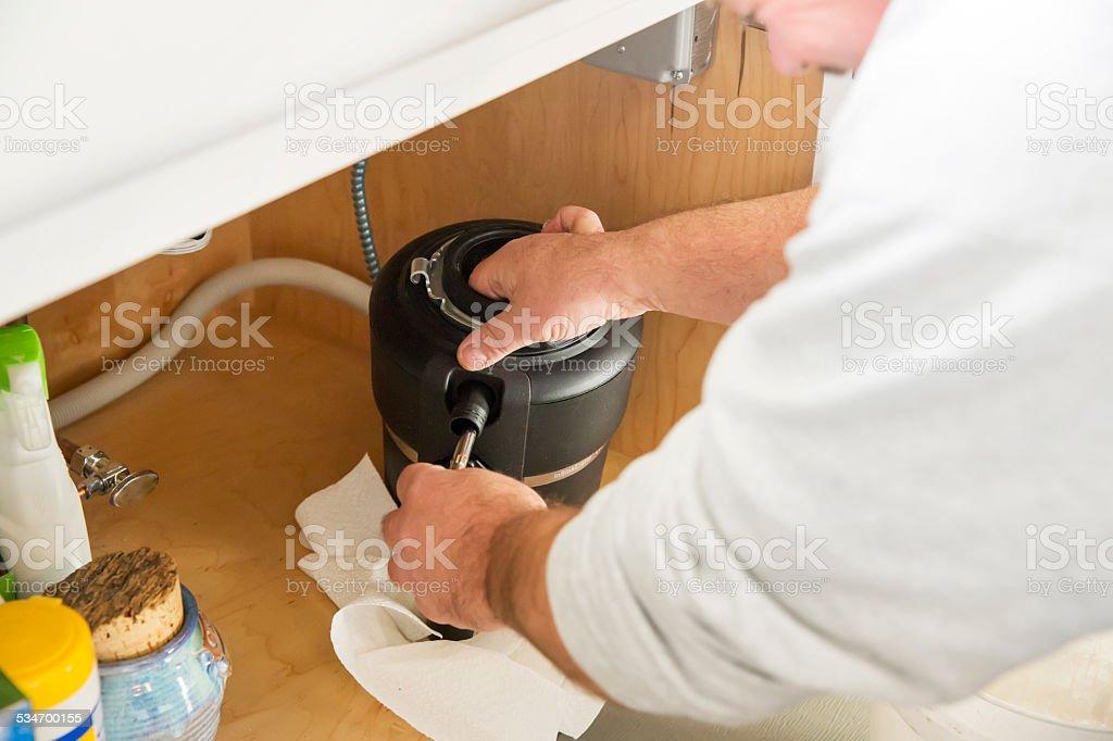 Plumber installs a new garbage disposal stock photo