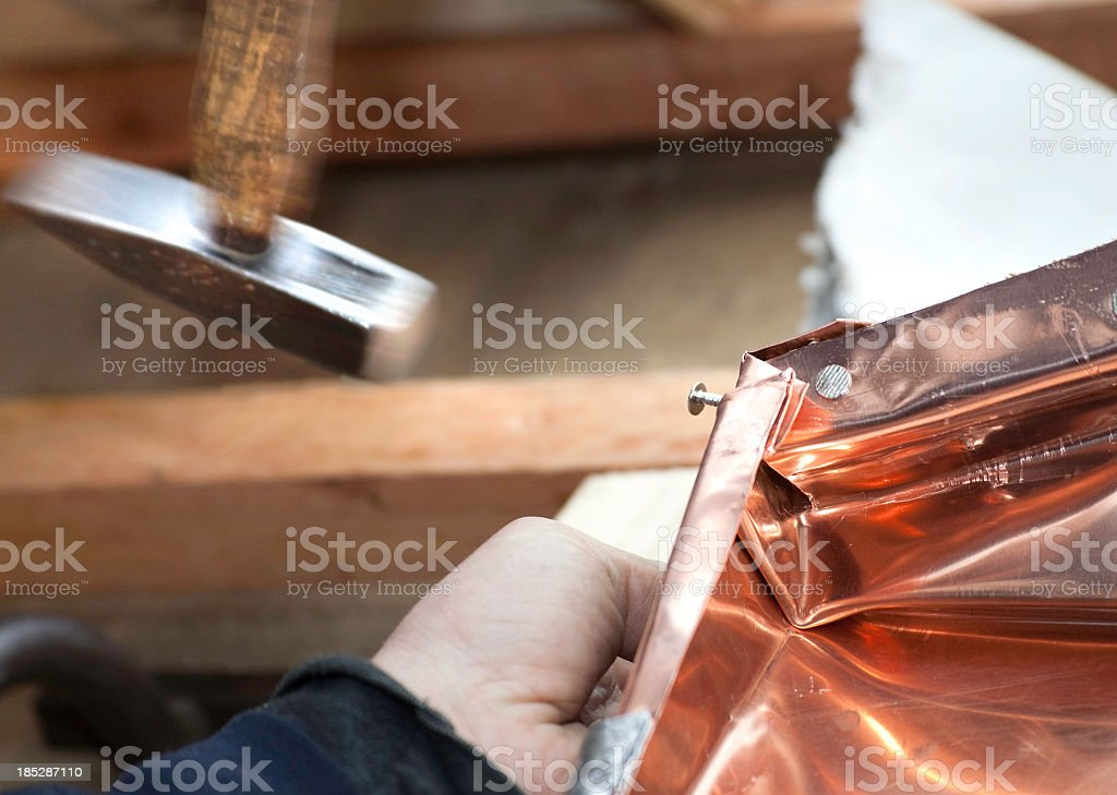 Plumber is working with hammer on a new copper gutter stock photo