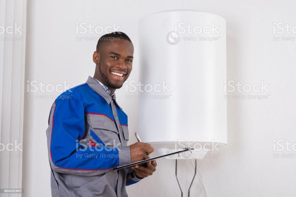 Plumber Looking At Electric Boiler stock photo