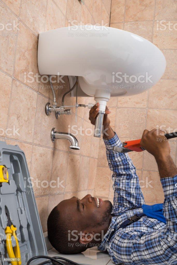 Plumber Lying On Floor Fixing Sink In Bathroom stock photo