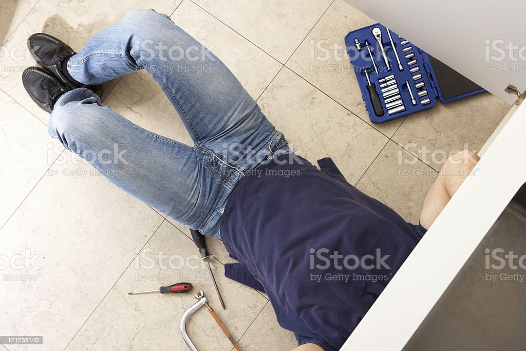 Plumber lying on his back working on sink royalty-free stock photo