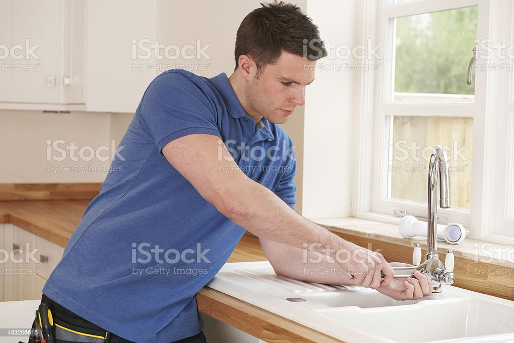 Plumber Mending Tap With Adjustable Wrench royalty-free stock photo