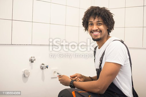 Young plumber man fixing a bathroom faucet. About 25 years old, African male.