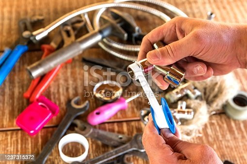 Plumber putting a teflon tape, closeup. Plumber tools on workshop table. Repair of water pipes. Sealing thread