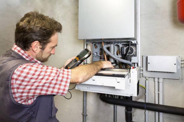 klempner einen condensing boiler reparieren - boiler stock-fotos und bilder
