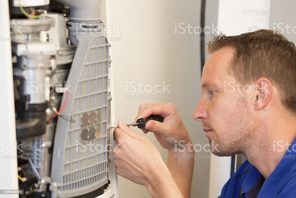 Plumber repairing a heater in house stock photo
