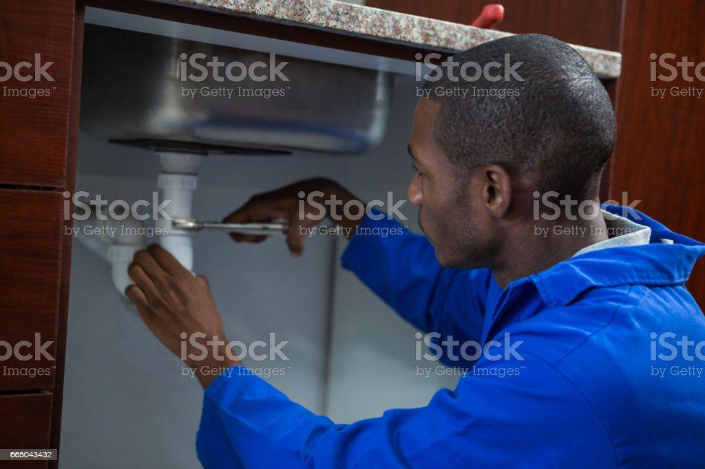 Plumber repairing a sink stock photo