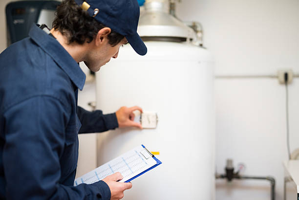 plumber repairing an hot-water heater - examining stock photos and pictures