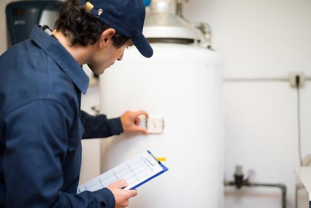 Plumber repairing an hot-water heater stock photo