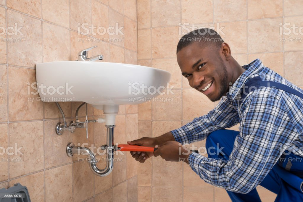 Plumber Repairing Sink In Bathroom stock photo