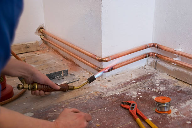Plumber soldering pipes attached to the wall stock photo