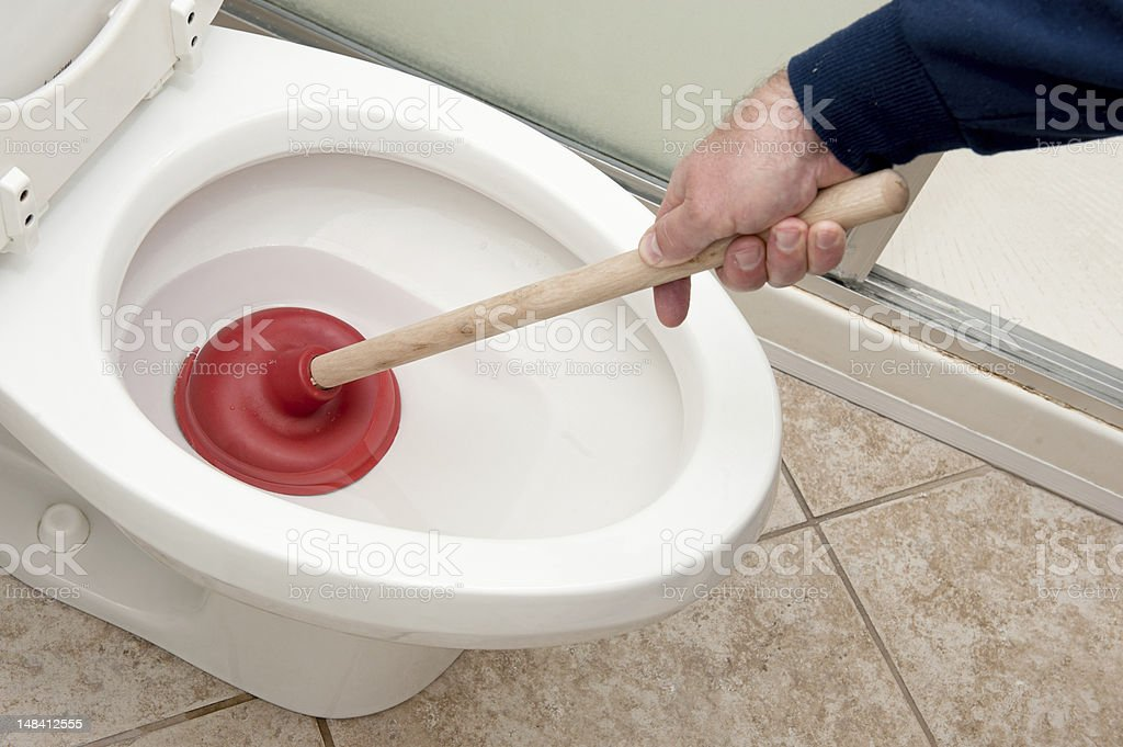 Plumber uncloging toilet A plumber uses a plunger to unclog a toilet. Airtight Stock Photo