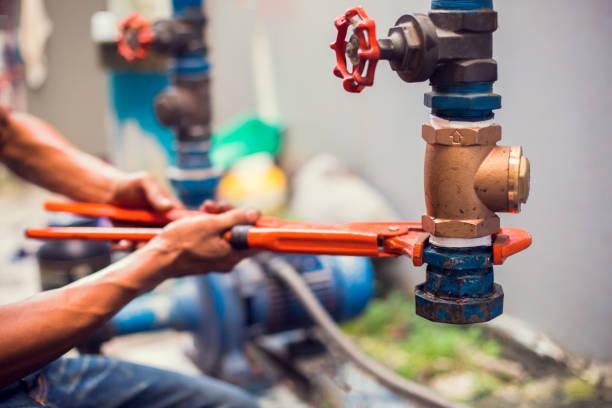 encanador usando uma chave inglesa para reparar e remover a tubulação e a válvula da fonte de água. - banheiro instalação doméstica - fotografias e filmes do acervo