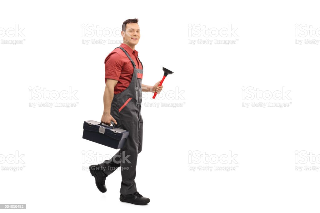 Plumber with a toolbox and a plunger walking stock photo