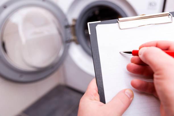 klempner mit klemmbrett in der nähe von waschmaschine - detektivhandwerk stock-fotos und bilder