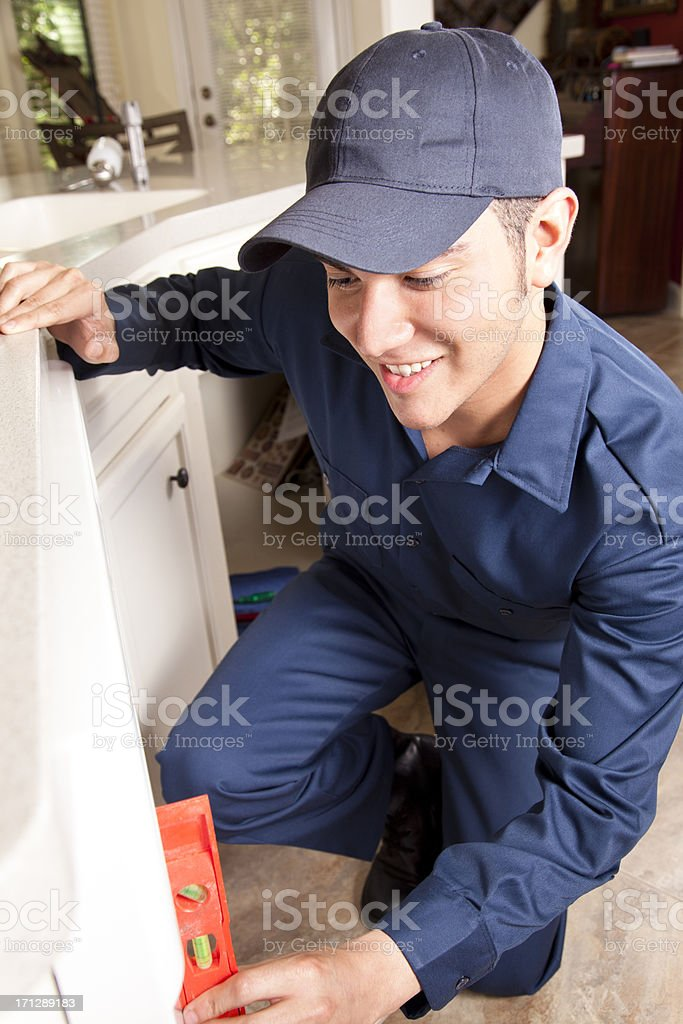 Plumber working on dishwasher in domestic kitchen royalty-free stock photo